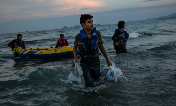 male refugees floating in by boat